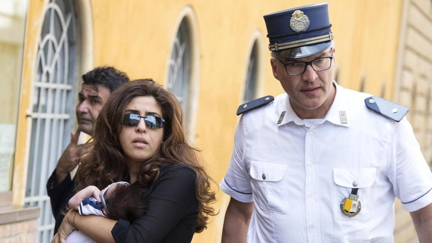 Public relations expert Francesca Chaouqui walks next a Vatican Gendarme as she arrives with her newly born son Pietro, at the Vatican for her trial, Monday, July 4, 2016.  Two Italian journalists who wrote books detailing Vatican mismanagement face trial in a Vatican courtroom along with three people accused of leaking them the information in a case that has drawn scorn from media watchdogs. (Maurizio Brambatti/ANSA via AP Photo)