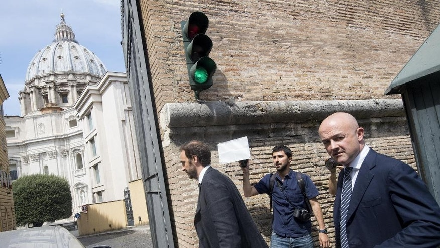 Italian journalists Gianluigi Nuzzi, right, and Emiliano Fittipaldi, left, arrive for a hearing of their trial, at the Vatican, Monday, July 4, 2016.  Two Italian journalists who wrote books detailing Vatican mismanagement face trial in a Vatican courtroom along with three people accused of leaking them the information in a case that has drawn scorn from media watchdogs. (Maurizio Brambatti/ANSA via AP Photo)