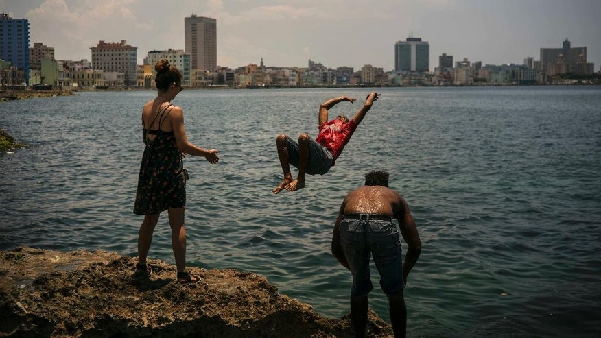 In this June 12, 2016 photo, the young Cuban American Maggie Sivit, left, looks at a youth jump into the ocean from the Havana's waterfront in Cuba. Sivit was brought to the island by CubaOne, a new program inspired by the reestablishment of diplomatic and business ties between the U.S. and Cuba. (AP Photo/Ramon Espinosa)