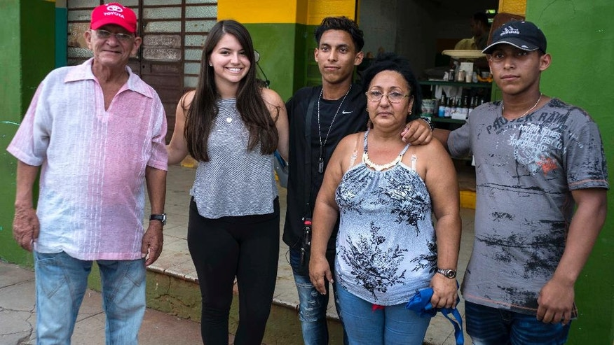 In this June 12, 2016 photo, Cuban American Miranda Hernandez, second left, poses with members of her extended family in Havana, Cuba. Hernandez was brought to the island by CubaOne, a new program inspired by the reestablishment of diplomatic and business ties between the U.S. and Cuba. (AP Photo/Ramon Espinosa)