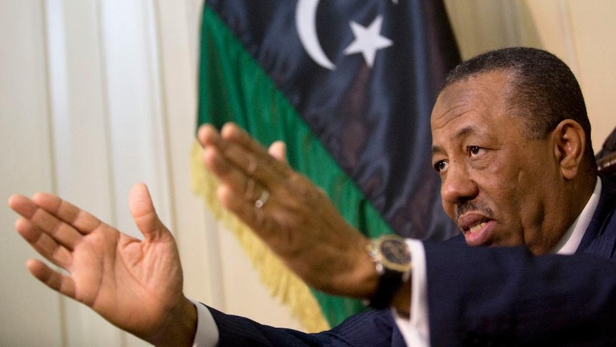 Libyan Prime Minister Abdullah al-Thinni, speaks during an interview with the Associated Press at the Libyan embassy in Cairo, Egypt, Tuesday, July 5, 2016. Al-Thinni of the interim government based in the eastern region, told The Associated Press that the UN-brokered deal has reached a deadlock. The deal must be amended, he said. Libyan flag seen at background. (AP Photo/Amr Nabil)
