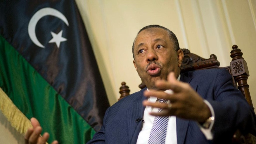 Libyan Prime Minister Abdullah al-Thinni, speaks during an interview with the Associated Press at the Libyan embassy in Cairo, Egypt, Tuesday, July 5, 2016. Al-Thinni of the interim government based in the eastern region, told The Associated Press that the UN-brokered deal has reached a deadlock. The deal must be amended, he said. Libyan flag seen at background.(AP Photo/Amr Nabil)