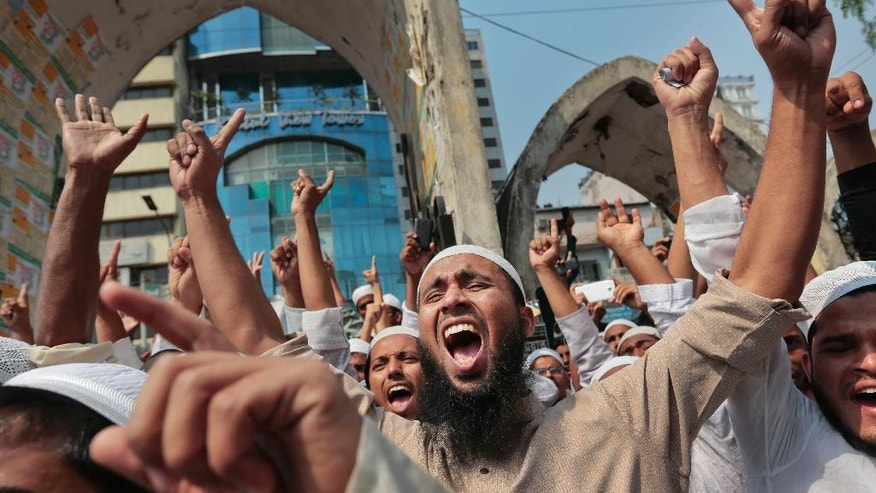 FILE - In this March 25, 2016, file photo, Bangladeshi activists of various Islamic political groups and other Muslims shout slogans after Friday prayers during a protest in Dhaka, Bangladesh. The July 1, 2016 deadly attack, the worst in a wave of violence waged by radical Islamists in recent years, speaks to a deeper divide within the nation of 160 million - one that has pitted secularists against those yearning for Islamic rule since the country won independence from Pakistan in a bloody war in 1971. (AP Photo, File)