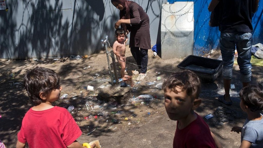 A woman bathes a child under a tap at a makeshift migrants and refugees camp situated meters away from the Serbian border with Hungary, in Horgos, Serbia, Monday, July 4, 2016. Waiting in the summer heat with limited running water, hundreds of refugees camping out on the Serbian-Hungarian border are facing uncertain prospects as EU nation Hungary prepares to implement new, tighter asylum rules on Tuesday. (AP Photo/Marko Drobnjakovic)