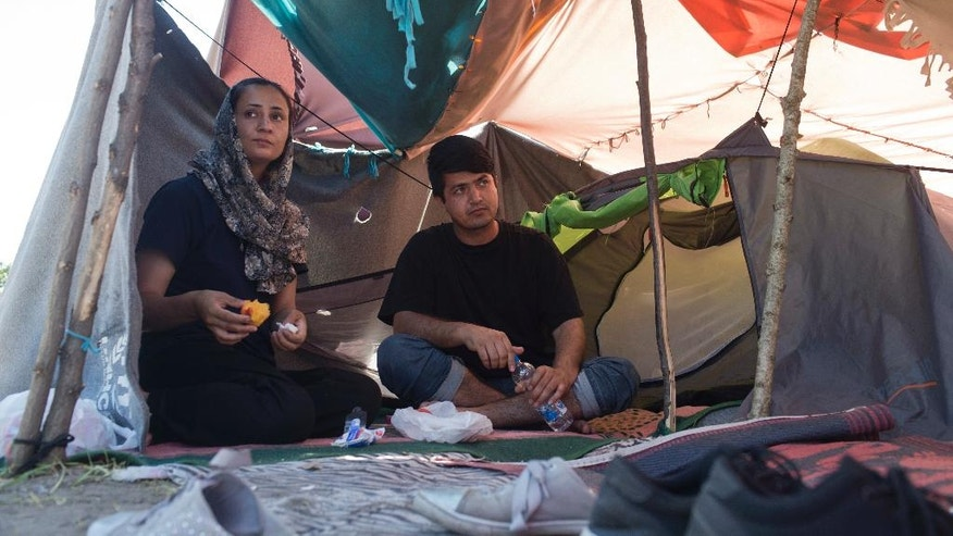 Azada Sayed, 23, left, and her husband, Hameed, 28, sit in their tent at a makeshift camp for migrants and refugees situated meters away from the Serbian border with Hungary, in Horgos, Serbia, Monday, July 4, 2016. Waiting in the summer heat with limited running water, hundreds of refugees camping out on the Serbian-Hungarian border are facing uncertain prospects as EU nation Hungary prepares to implement new, tighter asylum rules on Tuesday. (AP Photo/Marko Drobnjakovic)