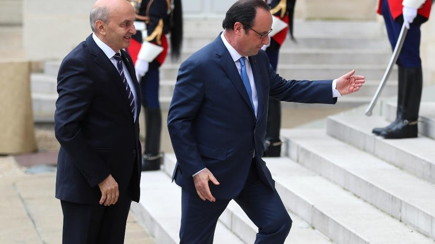 France's President Francois Hollande, right, welcomes Prime Minister of Kosovo Isa Mustafa, prior to the Balkans summit, at the Elysee Palace, in Paris, Monday, July 4, 2016. The leaders of France, Germany, Italy and Balkan nations are meeting to better prevent extremists from sneaking in with migrants who are moving west across Europe. (AP Photo/Thibault Camus)
