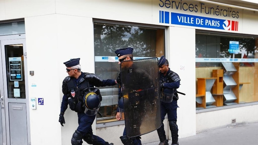 Riot police officers take position by an undertaker service during a demonstration in Paris, Tuesday, July 5, 2016. French unions are staging what's likely to be their last show of force against a labor bill that has divided the nation and prompted the worst social unrest in years.  The government says the bill — which makes it easier for companies to hire and fire employees and extend working hours — would boost hiring. (AP Photo/Francois Mori)