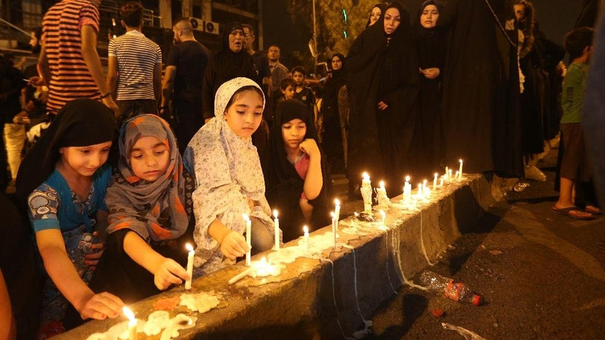 People light candles at the scene of a massive car bomb attack in Karada, a busy shopping district where people were shopping for the upcoming Eid al-Fitr holiday, in the center of Baghdad, Iraq, Monday, July 4, 2016. (AP Photo/Hadi Mizban)