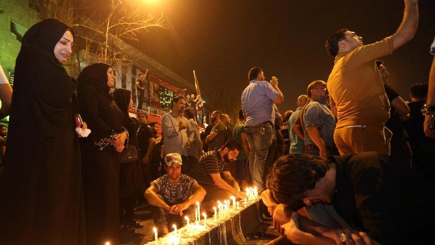 Iraqi women grieve as people light candles at the scene of a massive car bomb attack in Karada, a busy shopping district where people were shopping for the upcoming Eid al-Fitr holiday, in the center of Baghdad, Iraq, Monday, July 4, 2016. (AP Photo/Hadi Mizban)