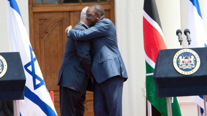 "Israeli Prime Minister Benjamin Netanyahu, second left, and Kenyan President, Uhuru Kenyatta , right, embrace at State House in Nairobi, Kenya, Tuesday, July 5, 2016. Netanyahu said his country's raid on Uganda's Entebbe airport 40-years ago, in which his brother was killed, ""changed the course"" of his life and had a lasting influence on his country's relations with Africa.  (AP Photo/Sayyid Abdul Azim)"