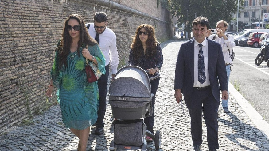 Public relations expert Francesca Chaouqui, center, arrives, with her newly born son Pietro, and her husband Corrado Lanino, second from left, at the Vatican for her trial, Tuesday, July 5, 2016.  Two Italian journalists who wrote books detailing Vatican mismanagement face trial in a Vatican courtroom along with three people accused of leaking them the information in a case that has drawn scorn from media watchdogs. (Giuseppe Lami/ANSA via AP Photo)