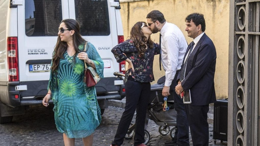 Public relations expert Francesca Chaouqui, second from left, kisses her husband Corrado Lanino, as they arrive at the Vatican for her trial, Tuesday, July 5, 2016.  Two Italian journalists who wrote books detailing Vatican mismanagement face trial in a Vatican courtroom along with three people accused of leaking them the information in a case that has drawn scorn from media watchdogs. (Giuseppe Lami/ANSA via AP Photo)