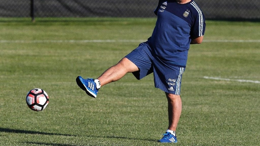 FILE - In this June 16, 2016 file photo, Argentina's soccer coach Gerardo Martino kicks the ball during a team practice at Harvard University in Cambridge, Mass. Argentina's Futbol Association confirmed on July 5, 2016 that Martino resigned from his post.  (AP Photo/Charles Krupa, File)