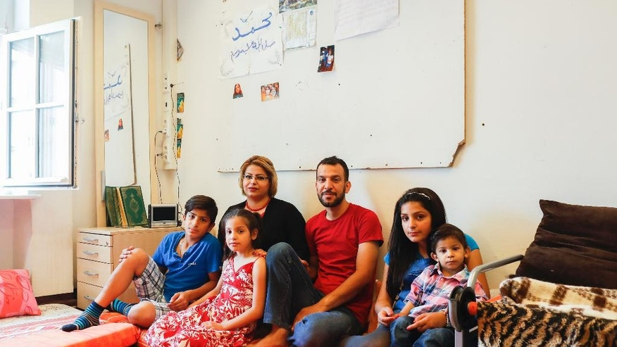 "Syrian refugees Moustafa Shikh Habib, center right, and his wife Susan Sheikha, center left, pose for a photo with their children, from left, Mohammed, Noor, Aysha and Mehdi at a room in the refugee shelter where they live, on the Islamic holiday of Eid al-Fitr, the end of the fasting month of Ramadan in Berlin, Germany, Tuesday, July 5, 2016. ""It's difficult to be away from all the family, from my brothers, on this special day,"" the 36-year-old Kurd Moustafa said at his new home in Berlin, two little cramped rooms he shares with his family. (AP Photo/Markus Schreiber)"