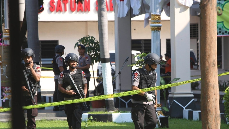 July 5, 2016: Members of police bomb squad examine the surrounding area near where a suicide bomber blew himself up at the local police headquarters in Solo, Central Java, Indonesia.