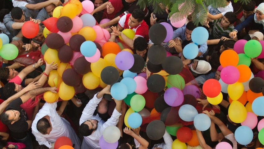 Egyptians try to catch balloons distributed for free after Eid al-Fitr prayers, marking the end of the Muslim holy fasting month of Ramadan outside al-Seddik mosque in Cairo, Egypt, Wednesday, July 6, 2016. (AP Photo/Amr Nabil)