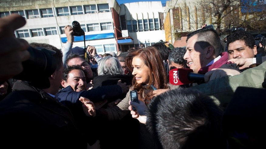 Argentina's former President Cristina Fernandez is surrounded by the press and supporters as she leaves federal court in Buenos Aires, Argentina, Wednesday, July 6, 2016. Fernandez appeared in court to be notified that she is accused of an alleged scheme to manipulate Argentina's currency. (AP Photo/Victor R. Caivano)