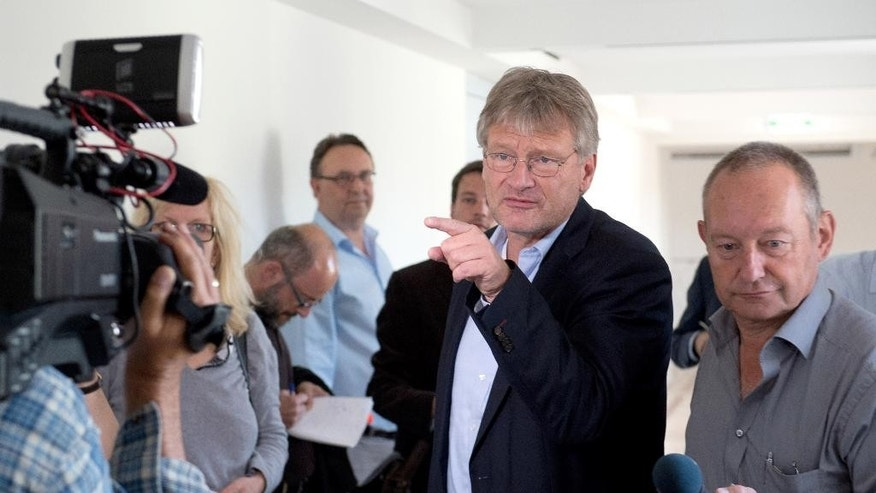 Joerg Meuthen, co-leader of the party Alternative for Germany or AfD passes waiting journalists in Stuttgart, Germany, wednesday, July 6, 2016. An argument over a regional lawmaker accused of anti-Semitism has laid bare divisions in the leadership of AfD. Thirteen out of 23 lawmakers left the caucus of AfD, in the southwestern state of Baden-Wuerttemberg on Tuesday, July 5, including Meuthen. (Bernd Weissbrod/dpa via AP)