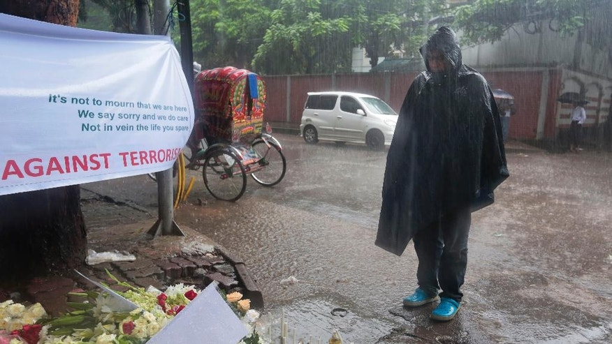 A Bangladeshi man stands in the rain and pays his respects to the victims of the attack on Holey Artisan Bakery, in Dhaka, Bangladesh, Tuesday, July 5, 2016. The attack, the worst convulsion of violence yet in the recent series of deadly attacks to hit Bangladesh, has stunned the traditionally moderate Muslim nation and raised global concerns about whether it can cope with increasingly strident Islamist militants. (AP Photo)