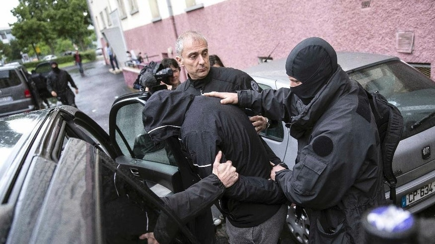 FILE - This Tuesday May 13, 2014 file photo shows French police officers detaining a suspect during a raid in a Strasbourg suburb, eastern France. The interior minister says police have arrested six people in northeastern France in a roundup of suspected jihadists who travelled to fight in Syria's civil war. A French court on Wednesday convicted seven young men who returned from weeks among the ranks of Islamic State extremists in Syria, including the brother of one of the suicide attackers who targeted Paris in November. (AP Photo/Jean Francois Badias, File)