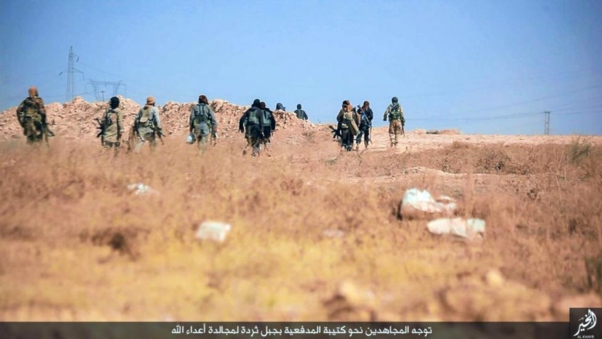 "This undated picture released on Tuesday, June. 28, 2016, by a militant website, which has been verified and is consistent with other AP reporting, shows fighters from the Islamic State group moving forward to fight against Syrian troops and pro-government gunmen, at al-Tharda mountain in Deir el-Zour province, Syria. The Arabic caption on the photo reads, ""The Mujahdeens heading toward al-Tharda mountain to engage enemies of Allah."" Turkey has been building a concrete wall along parts of border with Syria, trying to shut down what has long been a jihadi highway for Islamic State group fighters crossing from Turkey into Syria. According to exclusive Islamic State documents leaked to the Syrian opposition news site Zaman al-Wasl and analyzed by The Associated Press, at least 4,000 foreign IS recruits traveled through Turkey into Syria between late 2013 and most of 2014. (Militant photo via AP)"