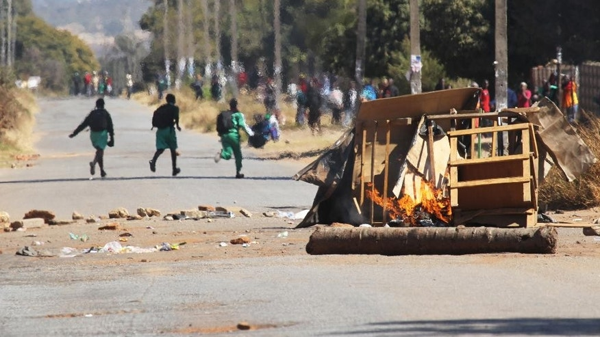 Schoolchildren run past a burning barricade, following a job boycott called via social media platforms, in Harare, Wednesday, July,6, 2016. A job boycott has shut down most of Zimbabwe as discontent deepens over increasing economic hardships in the southern Africa country. (AP Photo/Tsvangirayi Mukwazhi)