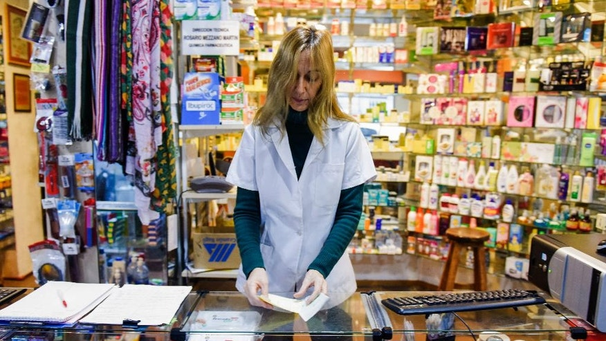 In this June 23, 2016 photo, pharmacist Rossana Rilla works at her own drugstore in downtown Montevideo, Uruguay. In her 28 years as a pharmacist, she has been beaten, dragged across the floor and threatened by thieves at gunpoint and with a grenade. She fears that selling marijuana will only make her store a bigger target for thieves and burglaries by drug dealers. (AP Photo/Matilde Campodonico)