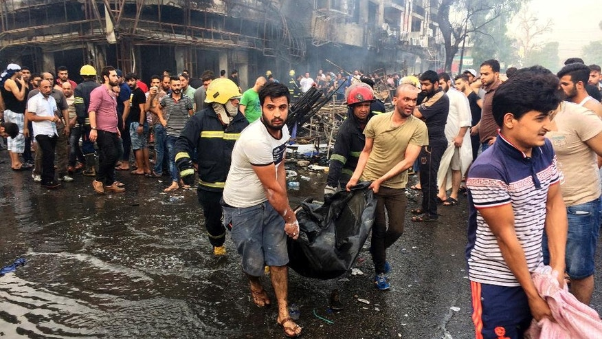 FILE -- In this Sunday July 3, 2016, file photo, Iraqi firefighters and civilians carry bodies of victims killed in a truck bomb at a commercial area in Karada neighborhood, Baghdad, Iraq. As millions of Muslims around the world celebrate the end of Ramadan, many are struggling to come to grips with what has been a particularly bloody month of attacks that killed more than 350 people and spread terror across continents. . (AP Photo/Khalid Mohammed, File)