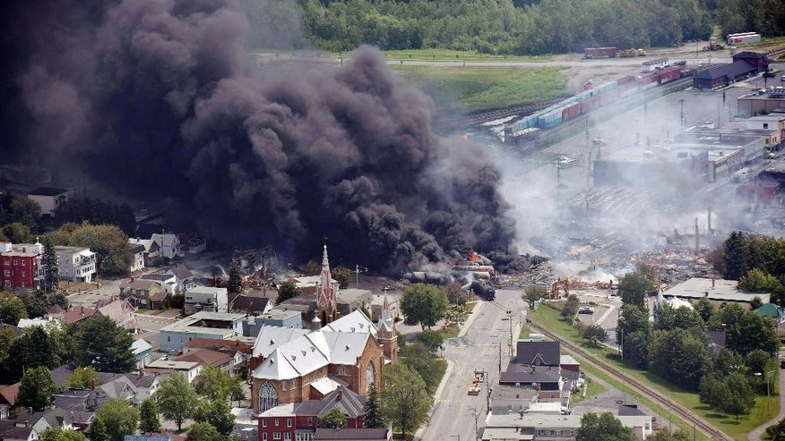 FILE - In this July 6, 2013, file photo, smoke rises from railway cars from now-defunct Montreal, Maine & Atlantic Railways company that were carrying crude oil after derailing in downtown Lac Megantic, Quebec, Canada. Forty-seven people were killed and 30 buildings burned in the town's center. Montreal, Maine and Atlantic Railway filed for bankruptcy after the tragedy. Three years later, residents are pressing the federal and provincial governments to re-route the rail to bypass the town. The new owner of the tracks, Central Maine & Quebec Railroad, spent millions of dollars to improve safety before resuming shipments of hazardous materials in the fall of 2014. Trains now are limited to 10 mph while traveling through town. (Paul Chiasson/The Canadian Press via AP, File)