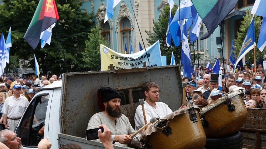 Drummers take part in a march as several thousand protesters carry trade union flags during a rally against the increase of prices for electricity, gas and housing outside of the Ukrainian parliament in Kiev, Ukraine, Wednesday, July 6, 2016. (AP Photo/Sergei Chuzavkov)