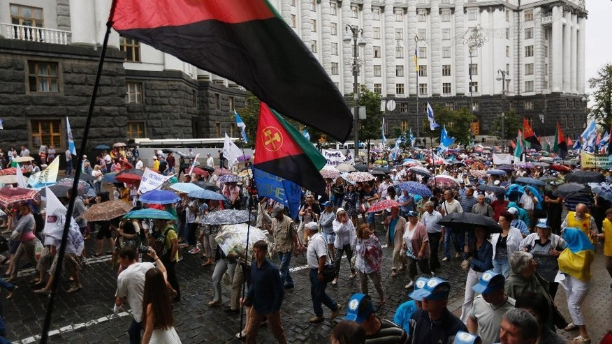 Protesters carry trade union flags as they march during a rally against the increase of prices for electricity, gas and housing outside of the Ukrainian parliament in Kiev, Ukraine, Wednesday, July 6, 2016. (AP Photo/Sergei Chuzavkov)