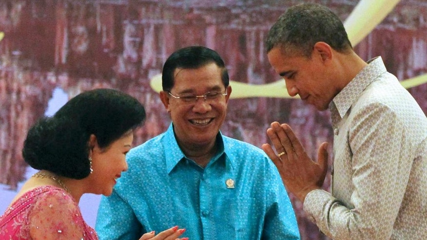 RETRANSMISSION WITH CORRECT SLUG -  FILE- In this Monday, Nov. 19, 2012 file photo, U.S. President Barack Obama, right, returns a greeting to Bun Rany, wife of Cambodian Prime Minister Hun Sen, center, prior to a gala dinner in Phnom Penh, Cambodia. An extensive network of businesses controlled by the family of Cambodia's longtime leader sustains and is sustained by his authoritarian rule, making foreign investment in the country risky, says a report issued Thursday, July 7, 2016 by the research and advocacy group Global Witness. With rapid economic growth for the past two decades along with a cheap labor force and minimal regulation, Cambodia has attracted foreign investment from the West as well as China. In 2015, Britain was the second-largest foreign investor in Cambodia after China. The United States is Cambodia's largest trading partner and export market. (AP Photo/Apichart Weerawong, File)