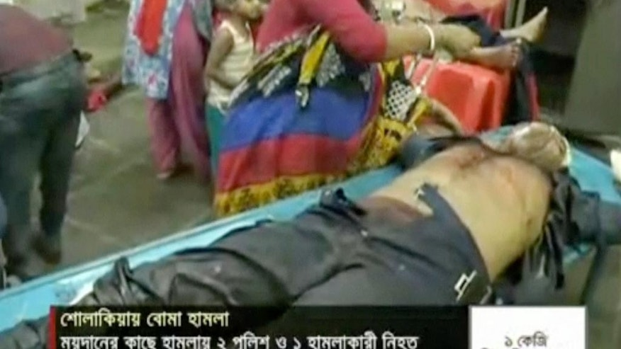 In this image made from video provided by Jamuna TV, injured people are assisted after a militant attack in Kishoreganj, about 90 kilometers (60 miles) north of the capital of Dhaka, Bangladesh, Thursday, July 7, 2016. Islamic extremists hurled homemade bombs and engaged in a gun battle with police guarding a large Eid prayer at the end of the holy Muslim month Thursday morning. The violence comes just days after a deadly hostage crisis at a restaurant in Dhaka. (Jamuna TV via AP Video)