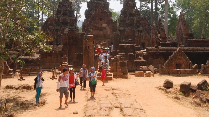 FILE - In this April 15, 2016, file, photo, tourist walk at Banteay Srey temple of Angkor complex, in Siem Reap province, about 320 kilometers (199 miles) north of Phnom Penh, Cambodia. Visitors who dress immodestly will not be allowed to enter Cambodia's famed Angkor temple complex, the agency that oversees the site said Thursday, July 7, 2016. (AP Photo/Heng Sinith, File)