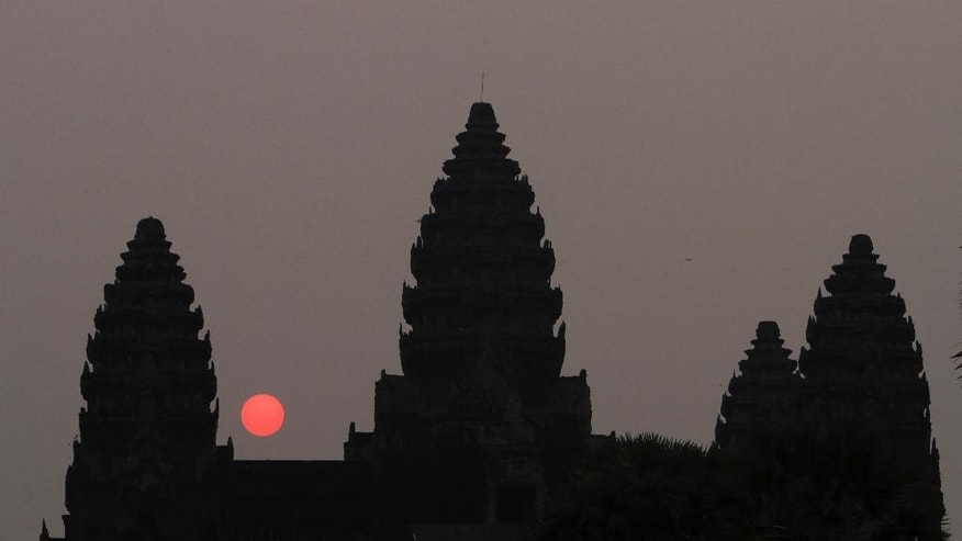 In this Friday, March 20, 2015, file photo, the sun rises behind Angkor Wat at the eastern site of Siem Reap province, some 230 kilometers (143 miles) northwest of Phnom Penh, Cambodia. Visitors who dress immodestly will not be allowed to enter Cambodia's famed Angkor temple complex, the agency that oversees the site said Thursday, July 7, 2016. (AP Photo/Heng Sinith, File)
