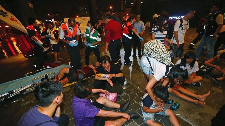 Injured people are helped by emergency rescue workers outside a station after an explosion on a passenger train in Taipei, Taiwan, Thursday, July 7, 2016. Taiwan's official news agency said an explosion that engulfed a commuter train car in flames has injured a number of people, some of them seriously. (AP Photo/Jerry Chen)
