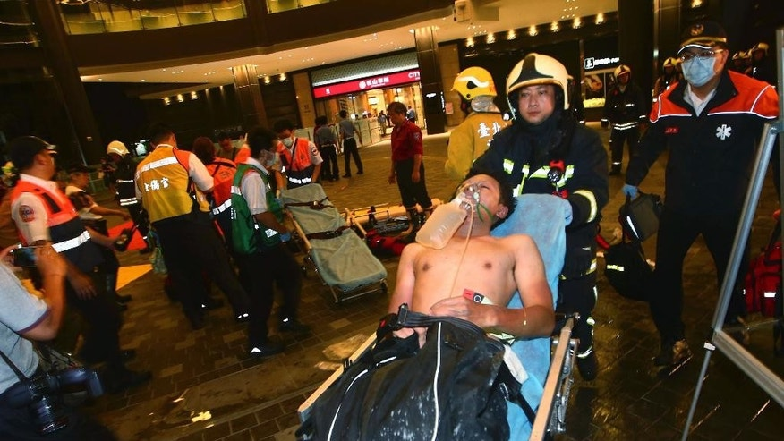 Injured people are helped by emergency rescue workers after an explosion on a passenger train in Taipei, Taiwan, Thursday, July 7, 2016. Taiwan's official news agency said an explosion that engulfed a carriage of a commuter train in flames wounded a number of people, some of them seriously. (AP Photo/Jerry Chen)