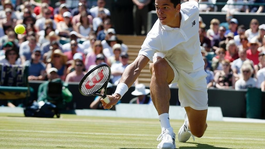 Milos Raonic of Canada returns a ball to Sam Querrey of the U.S during their men's singles match on day ten of the Wimbledon Tennis Championships in London, Wednesday, July 6, 2016. (AP Photo/Alastair Grant)