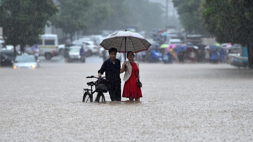 In this Wednesday, July 6, 2016 photo, a couple holding an umbrella in a rain wade through a flooded road in Wuhan in central China's Hubei province. Water levels are starting to recede in central and eastern China Thursday following a week of heavy downpours that have broken levees, flooded cities and villages, halted public transportation, and left at least hundreds people dead or missing.(Chinatopix via AP)
