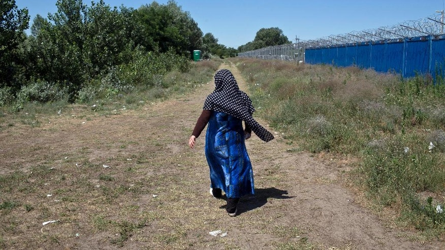 A woman walks next to border barriers at a makeshift migrants and refugees camp situated meters away from the Serbian border with Hungary, in Horgos, Serbia, Monday, July 4, 2016. Waiting in the summer heat with limited running water, hundreds of refugees camping out on the Serbian-Hungarian border are facing uncertain prospects as EU nation Hungary prepares to implement new, tighter asylum rules on Tuesday. (AP Photo/Marko Drobnjakovic)
