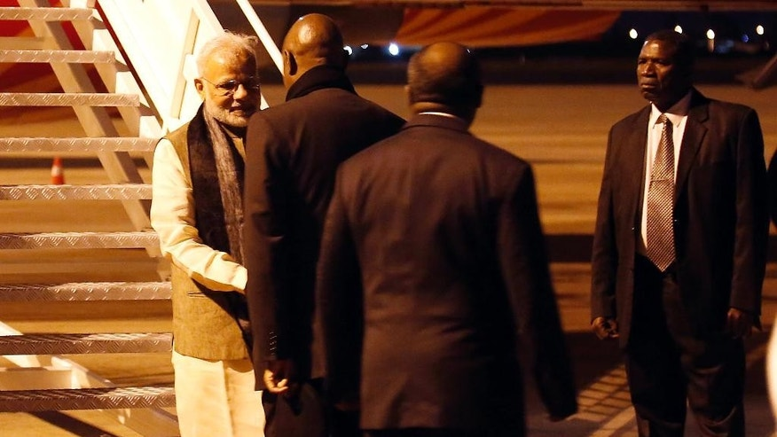 Indian Prime Minister Narendra Modi, left, greets officials as he arrives at the airport in Maputo, Mozambique, Thursday, July 7, 2016. India's prime minister has kicked off a four-nation African tour on a continent where China's presence has been strong, including countries that haven't been visited by an Indian leader in more than three decades.(AP Photo/Schalk van Zuydam)