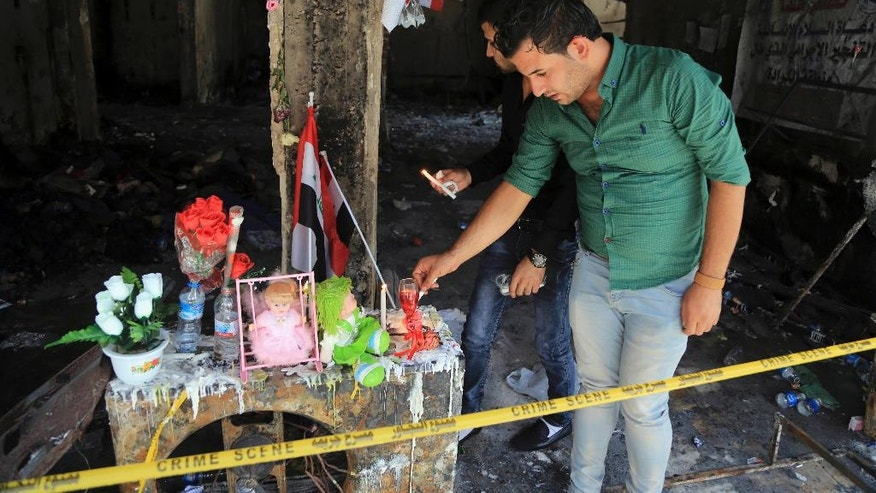 People light candles next to dolls belonging to Rabab Faris, 5, a bomb victim at the scene of Sunday's massive truck bomb attack in the Karada neighborhood, Baghdad, Iraq, Thursday, July 7, 2016. (AP Photo/Karim Kadim)