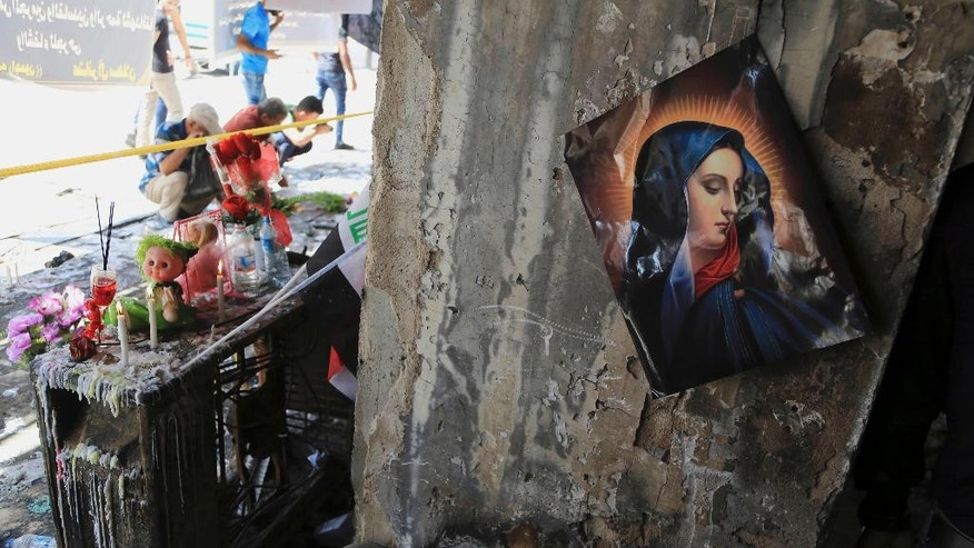 A picture of the Virgin Mary is fixed to a wall of a destroyed mall as Iraqis gather at the scene of Sunday's massive truck bomb attack in the Karada neighborhood, Baghdad, Iraq, Thursday, July 7, 2016. (AP Photo/Karim Kadim)