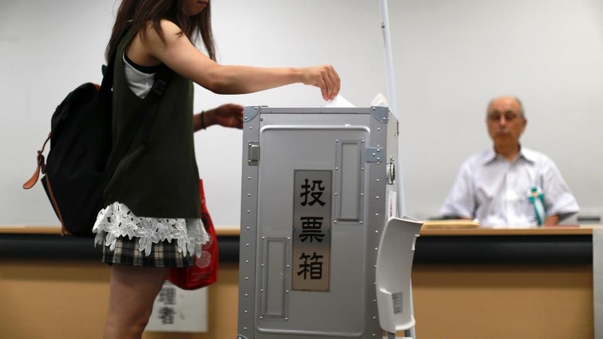 In this July 5, 2016 photo, Ayano Takeuchi, left, 19-year-old university student casts a ballot paper at an early voting polling place at Keio University in Yokohama, near Tokyo.  Some 2.4 million young person are newly eligible to vote in Sunday's election for the upper house of parliament, the first national election since Japan lowered the voting age last year from 20 to 18.  (AP Photo/Eugene Hoshiko)