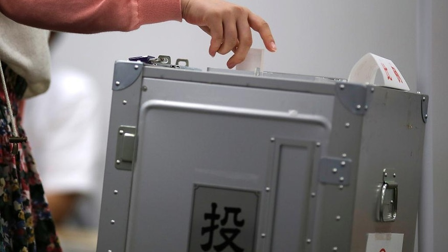 In this July 5, 2016 photo, a young voter cats a ballot paper near ballot box at an early voting polling place at Keio University in Yokohama, near Tokyo.  Some 2.4 million young person are newly eligible to vote in Sunday's election for the upper house of parliament, the first national election since Japan lowered the voting age last year from 20 to 18. (AP Photo/Eugene Hoshiko)