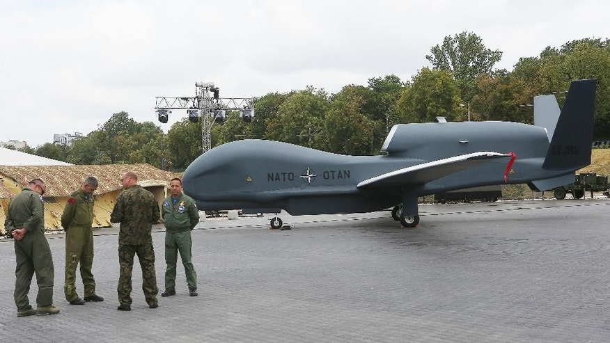 Soldiers stand near a NATO drone in front the National Stadium where the NATO summit will take place in Warsaw, Poland, Thursday, July 7, 2016. The Polish capital Warsaw will host a two-day NATO summit starting Friday, July 8, the first time ever that it hosts a top-level meeting of the Western military alliance which it joined in 1999. (AP Photo/Czarek Sokolowski)