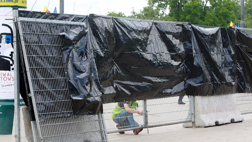 Workers install fences around the National Stadium, the venue of the upcoming NATO summit, in Warsaw, Poland, Wednesday, July 6, 2016. The Polish capital will host a two-day NATO summit starting Friday, the first time ever that it hosts a top-level meeting of the Western military alliance which it joined in 1999. (AP Photo/Czarek Sokolowski)