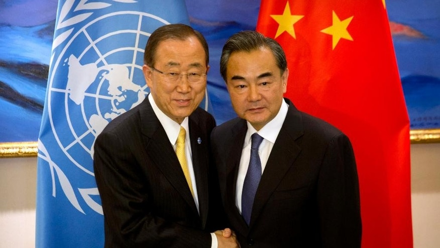 U.N. Secretary General Ban Ki-moon, left, shakes hands with Chinese Foreign Minister Wang Yi, right, at the Diaoyutai State Guesthouse in Beijing, Thursday, July 7, 2016. (AP Photo/Mark Schiefelbein, Pool)