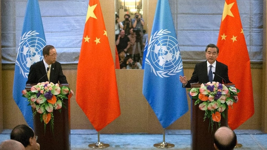Chinese Foreign Minister Wang Yi, right, speaks during a joint press conference with U.N. Secretary-General Ban Ki-moon at the Diaoyutai State Guesthouse in Beijing, Thursday, July 7, 2016. (AP Photo/Mark Schiefelbein)