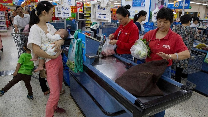 In this Wednesday, Nov. 11, 2015, photo, workers tend to customers paying for purchases at a Wal-Mart in Shenzhen, in southern China's Guangdong province. Wal-Mart faces protests by employees in China over what they say is a drastic change in work schedules under a system rolled out in June 2016 as the company overhauls its struggling business amid slowing economic growth and competition from e-commerce. (AP Photo/Ng Han Guan)